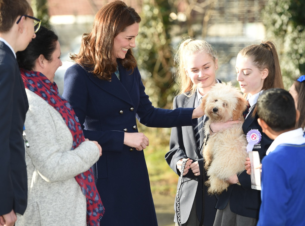 Pregnant Kate beams as she greets young fans during school visit