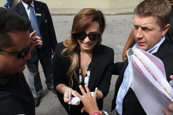 Demi Lovato atende fãs por porta de hotel