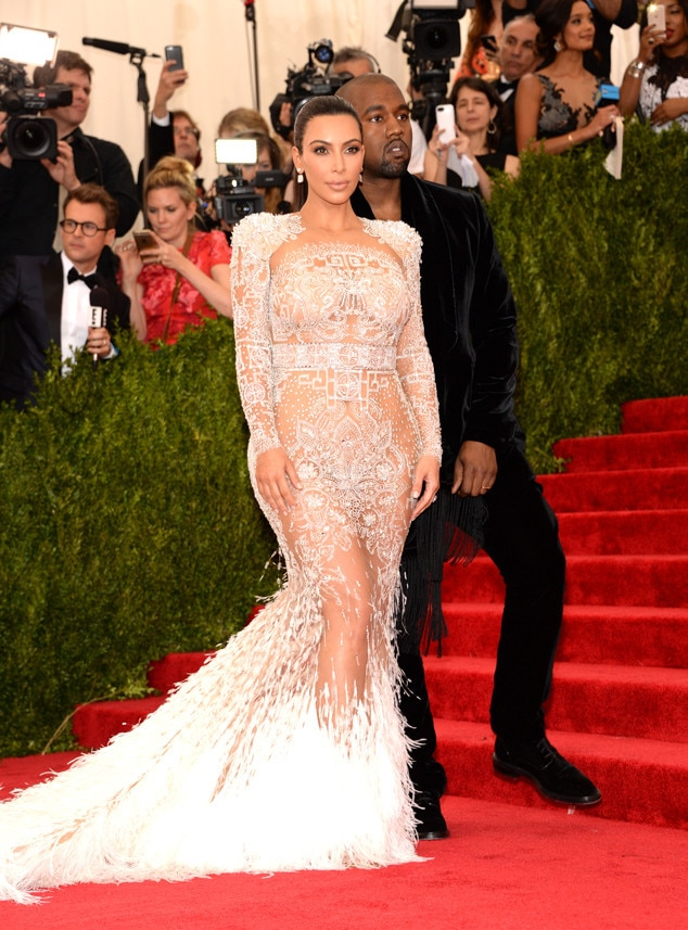 Feathered Frenzy -  Wowzers! Kim shuts it down at the 2015 Met Gala in an elegant nude Roberto Cavalli gown with feathered detailing on the train.