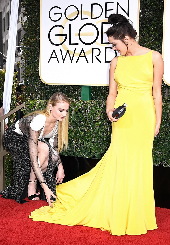 Mellow yellow -  The 23-year-old helps fix her friend's stunning yellow dress at the 2017 Golden Globes.