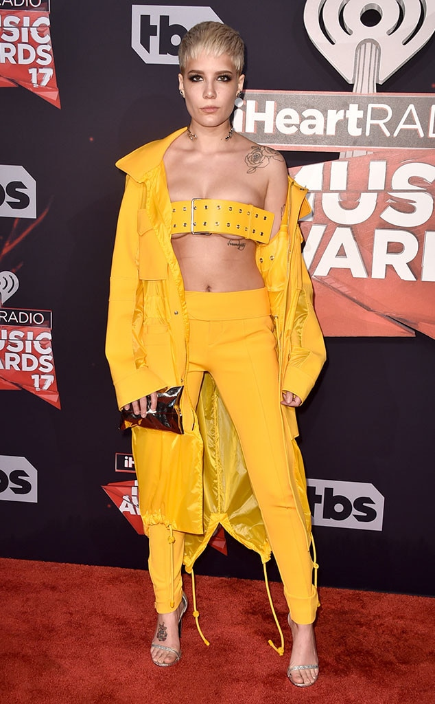 Halsey -  Halsey goes for the gold wearing an audacious marigold ensemble from the Versus Versace Spring 2017 collection. She rocks a wide belt as a top and pairs it with a matching yellow coat and pants.