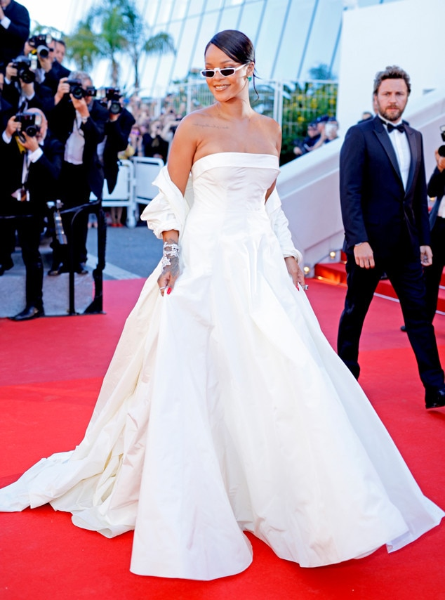 Rihanna -  The Fenty Beauty founder and  Ocean's 8  actress is a vision in white in her strapless Dior Haute Couture gown. In true Rihanna fashion, no detail is missed as she accessories with a matching shawl and sunnies.