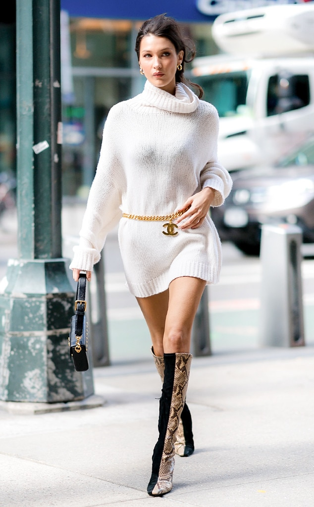 Bella Hadid -  On her way to her Victoria's Secret Fashion Show fitting, the model takes the sweater dress to the next level by completing the look with a gold chain belt by Chanel and snakeskin knee-high boots.