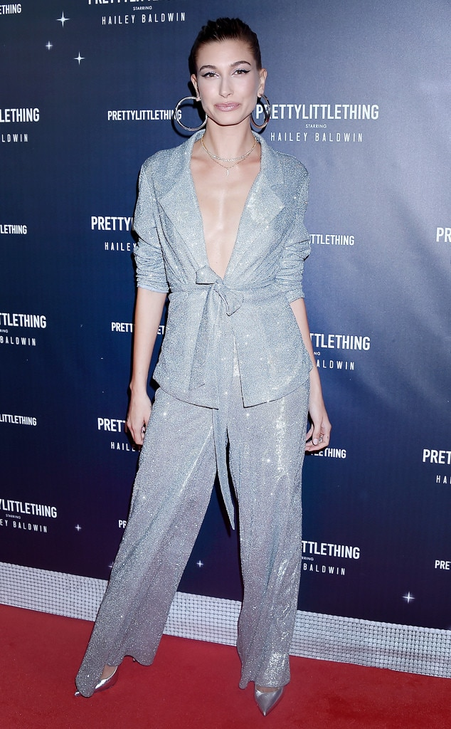 Hailey Baldwin -  In honor of her collaboration, the model poses in a metallic co-ord set, silver pumps and large hoops.