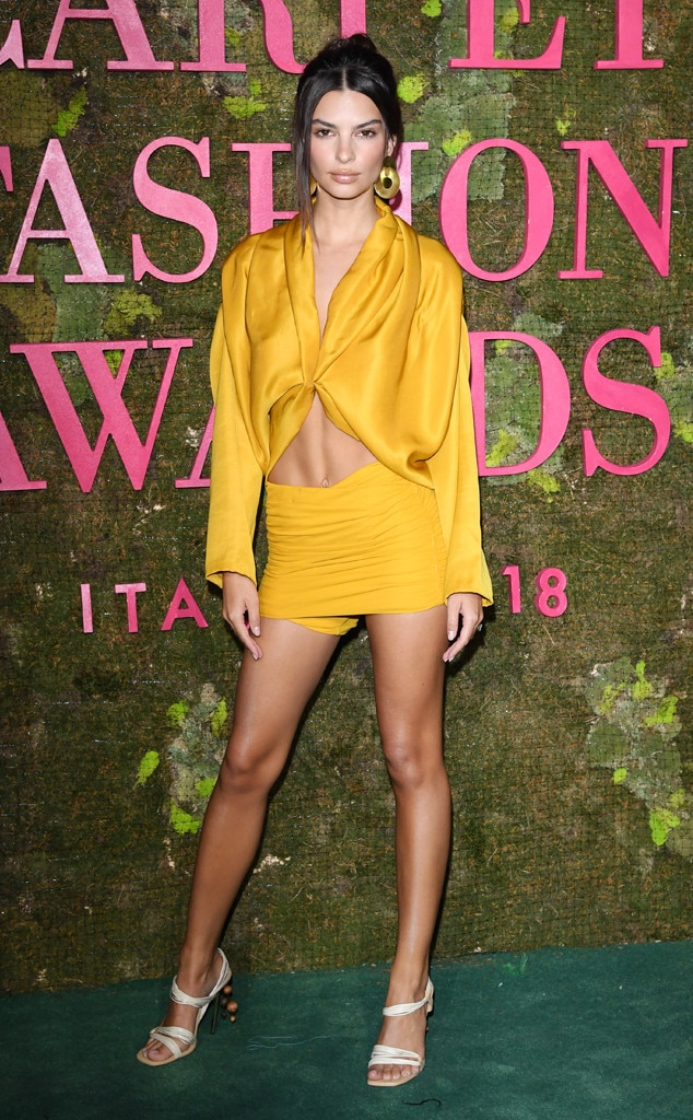 Wow Factor -  Model  Emily Ratajkowski  steals the spotlight at the Green Carpet Fashion Awards in Milan, wearing a Roberto Cavalli mustard yellow ensemble with gold double disc earrings and white strappy heels.