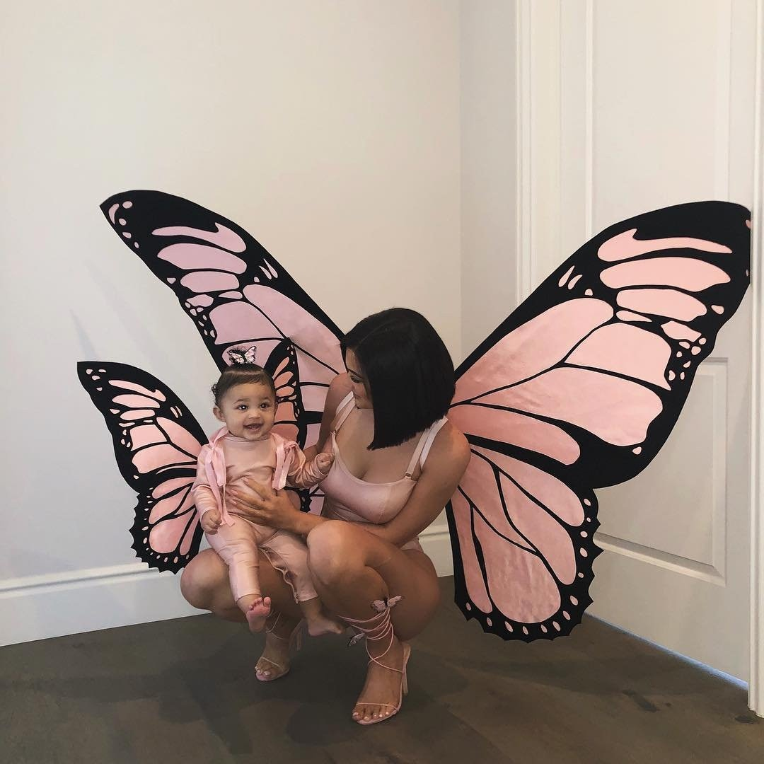 """Butterfly Effect -  The cosmetics mogul and her baby girl pay homage to Travis Scott 's song titled """"Butterfly Effect"""" with matching wings and light pink ensembles."""