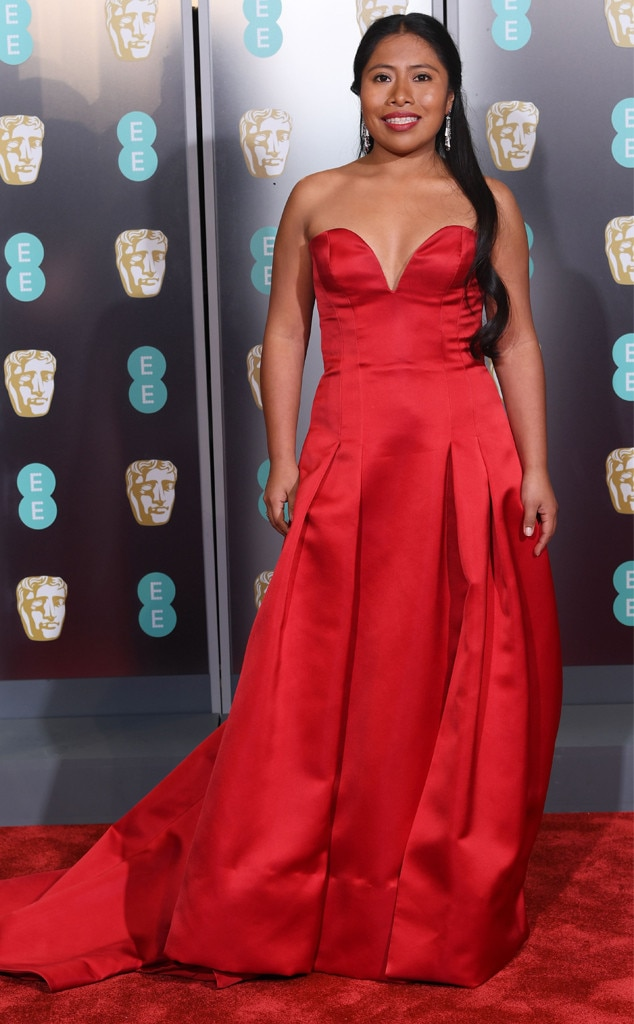 Radiant in Red -  Yalitza lights up the 2019 British Academy Film Awards red carpet in a custom Alberta Ferretti gown. Her dress is simple, yet striking as it features a sweetheart neckline and an A-line silhouette.