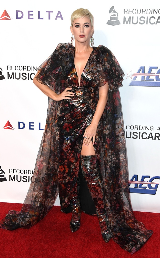 Dark Flower -  Singer Katy Perry wears a sheer dark floral cape over matching dress and boots while attending the MusiCares Person of the Year honoring Dolly Parton in Los Angeles.