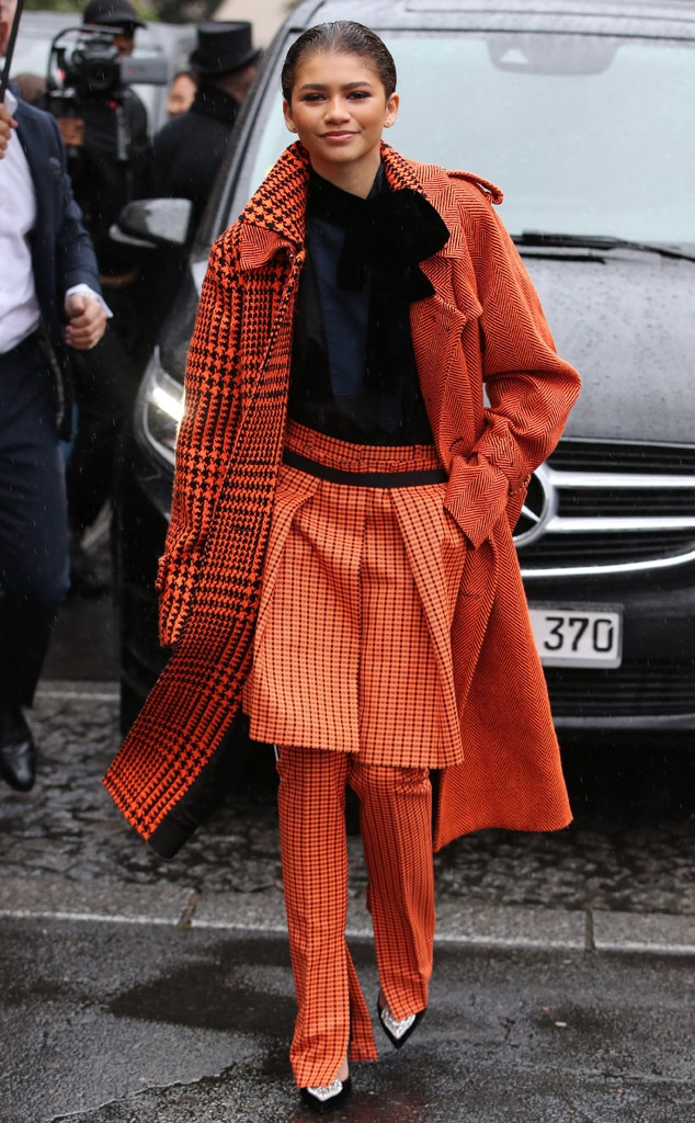 Channel Orange -  Actress  Zendaya rocks street style in an orange and black pant dress ensemble, paired with a statement orange coat during Paris Fashion Week. We love her suttle play with multiple prints!