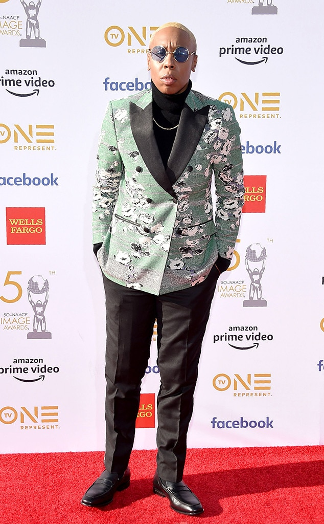 Lena Waithe - The Chi  writerpairsa green coat and black pants with some cool circular sunglasses on the red carpet.
