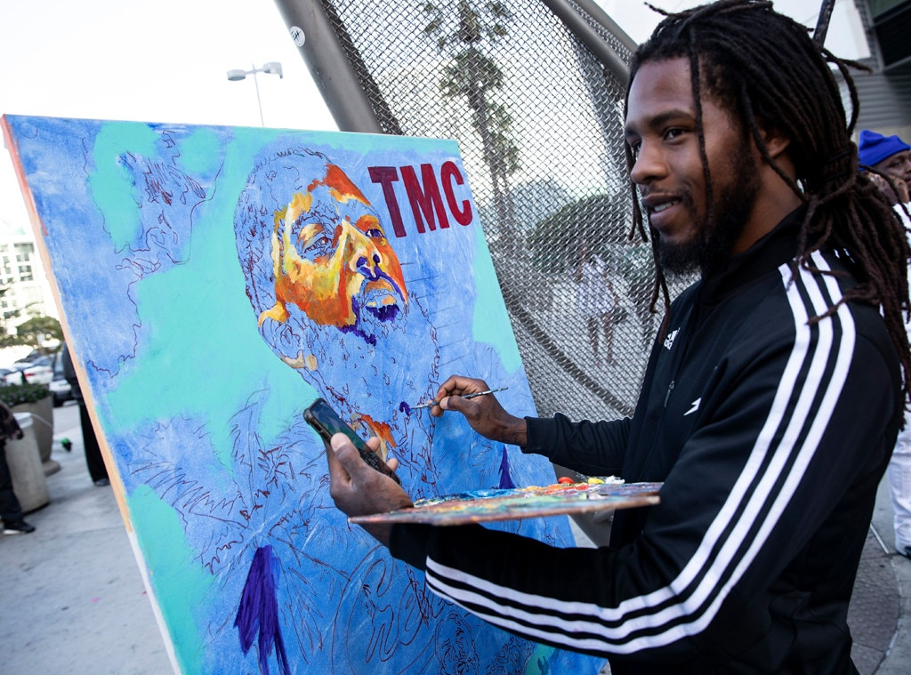 Portrait of Nipsey Hussle -  An artist is photographed painting a portrait of Nipsey Hussle outside of the Staples Center.