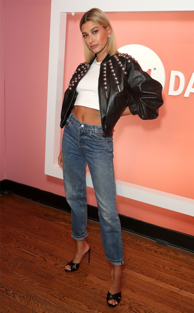 T-Shirt & Jeans -  Model  Hailey Bieber  wears a crop top and jeans dressed up with a studded leather jacket and heals while attending  Levi's 501 Day  in Los Angeles.