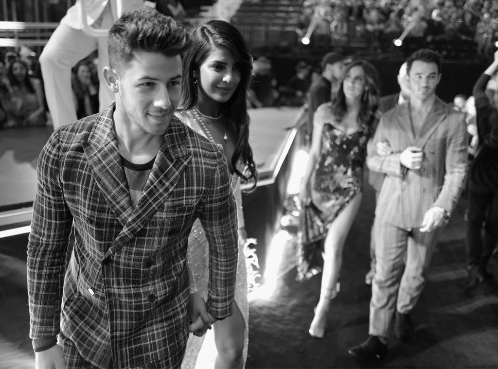 "Nick Jonas, Priyanka Chopra, Kevin Jonas & Danielle Jonas -  The ""Chains"" singer tenderly holds his wife's hand as they walk through the crowd."