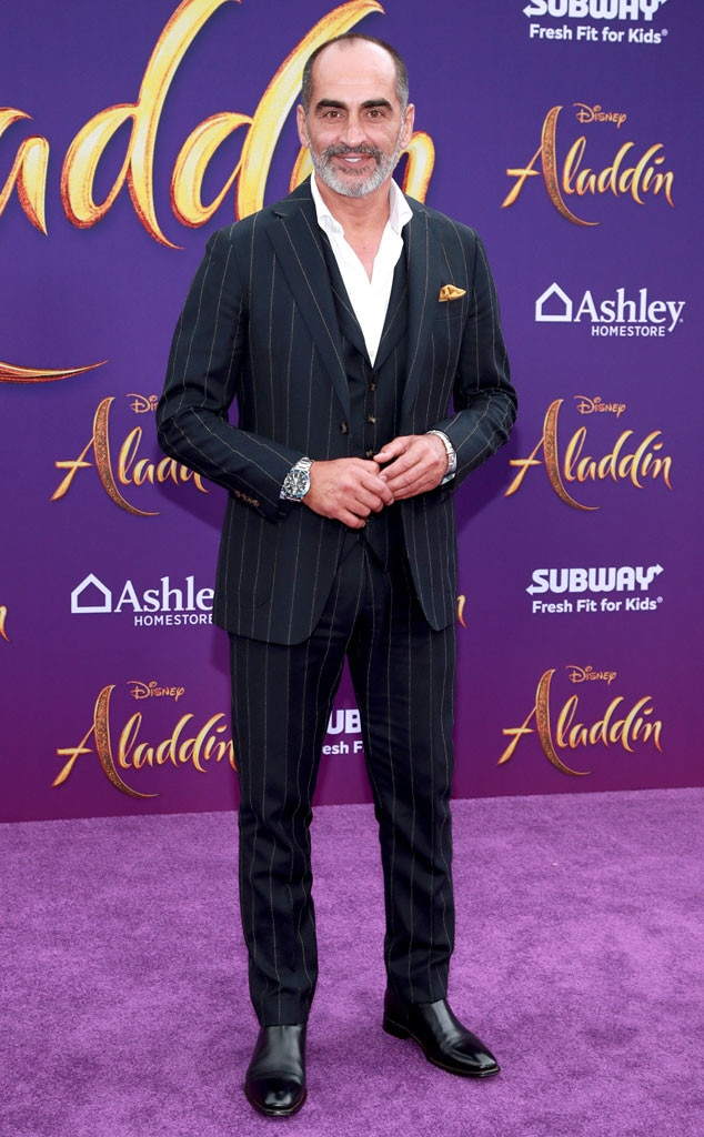 Navid Negahban -  The  Aladdin  star dons a timeless pin-stripe suit while posing for pictures on the purple carpet.