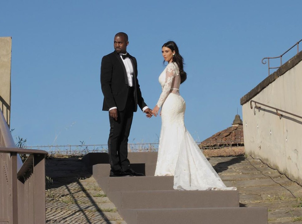 Husband & Wife -  Kim and Kanye are pictured side-by-side in their wedding attire, holding hands.
