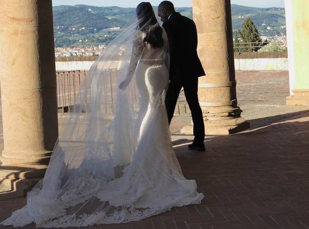 Bride & Groom -  The couple shows off their gorgeous wedding attire against the sprawling Tuscan landscape.