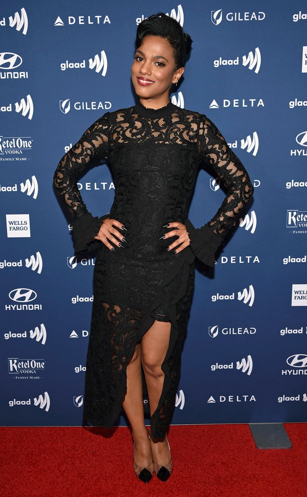 Freema Agyeman -  The Doctor Who  star smiles in a form-fitting black dress with lace trim across the top.