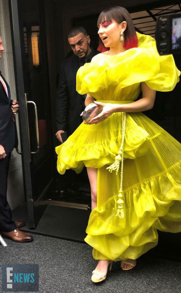 Charli XCX -  The singer steps out in yellow as she leaves her hotel for the fashion event.