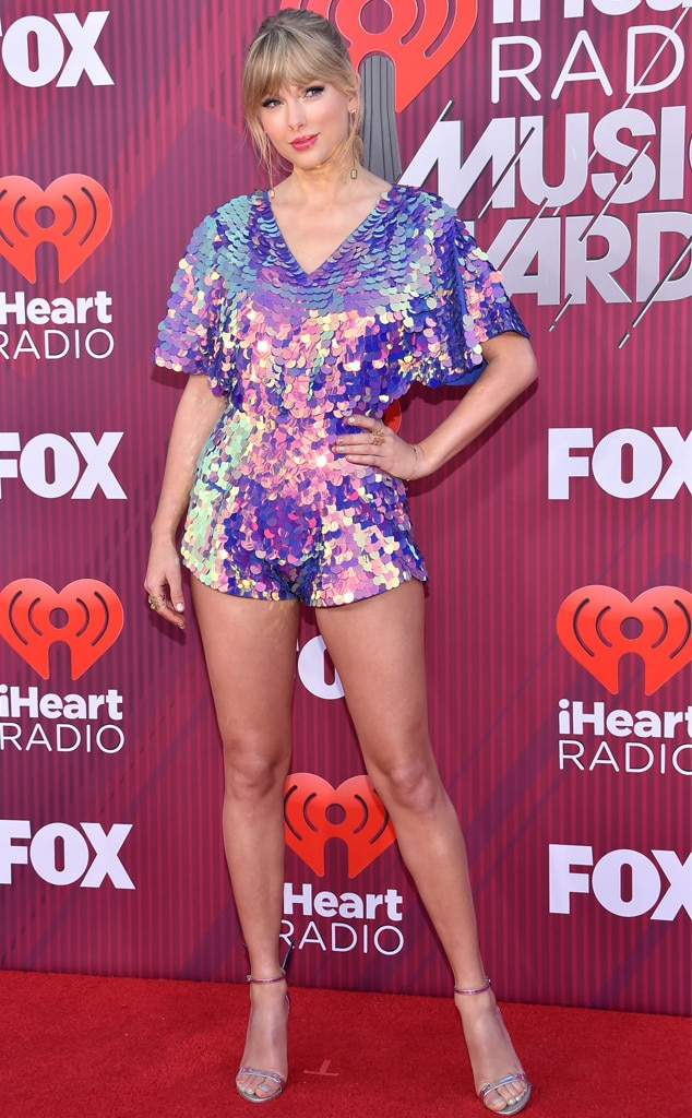 2019 iHeartRadio Music Awards -  Taylor turned heads on the red carpet in this shimmery purple romper before teasing new music was on the way.    Romper: Rosa Bloom Shoes: Sophia Webster